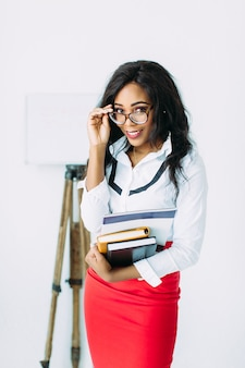 African business woman in glasses holding books and documents, standing on white
