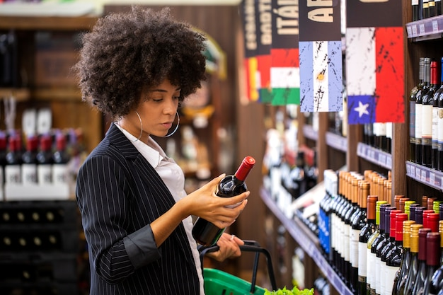 African business woman holding bottles of wine in supermarket.