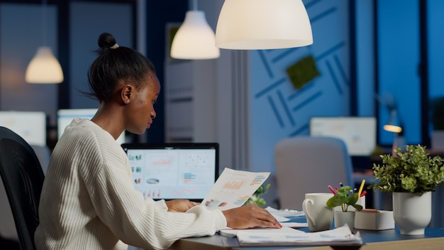 그래픽 및 재무 통계가 포함된 문서를 들고 있는 아프리카 비즈니스 여성은 창업 사무실에 앉아 있는 노트북 앞에서 초과 근무를 하고 있습니다. 프로젝트 기한을 준수하는 집중 직원