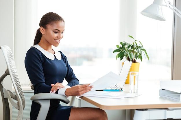 ドキュメントと職場のテーブルのそばに座ってドレスを着てアフリカのビジネス女性