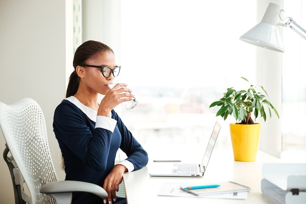 アームチェアに座って、オフィスで水を飲むドレスを着たアフリカのビジネス女性