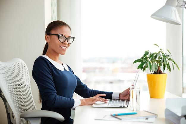 オフィスの肘掛け椅子に座ってカメラを見ているドレスを着たアフリカのビジネス女性。