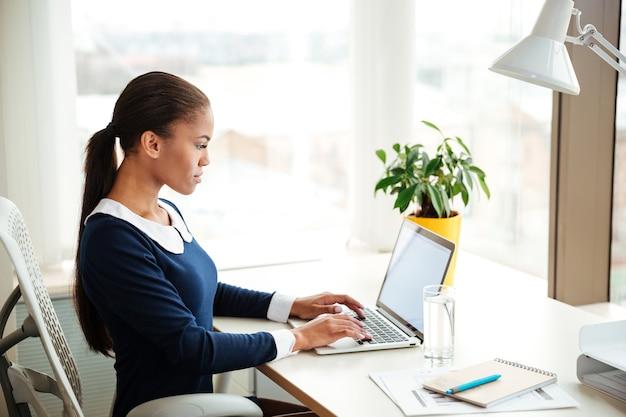 窓の近くの肘掛け椅子に座って、オフィスでラップトップを使用してドレスを着たアフリカのビジネス女性