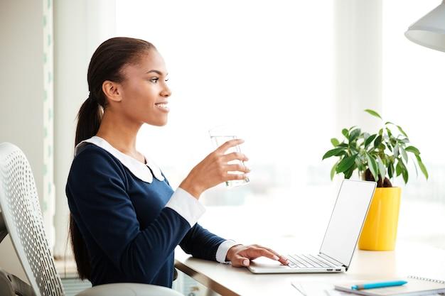 オフィスの窓の近くに水とアームチェアに座っているドレスを着たアフリカのビジネス女性