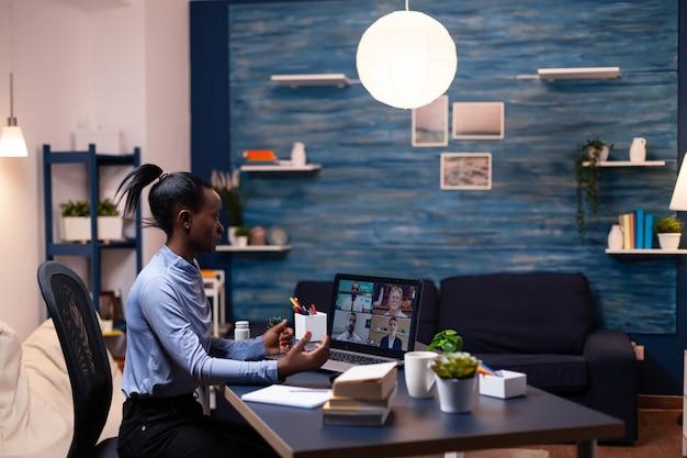 深夜の居間からのビデオ通話中に同僚の話を聞いているアフリカのビジネスウーマン。残業をしている仮想会議で話す最新のテクノロジーネットワークワイヤレスを使用します。