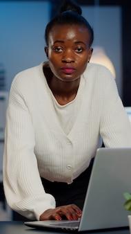 夜遅くにスタートアップ企業で働いているラップトップでメールを読んだ後、正面を見て机の近くに立っているアフリカのビジネスウーマン