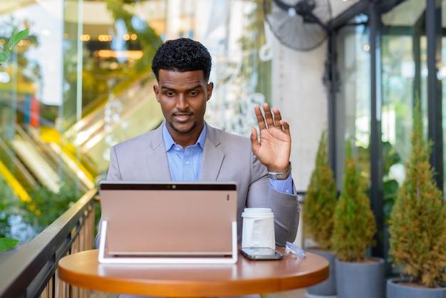 화상 통화를 위해 랩톱 컴퓨터를 사용하는 커피 숍에서 아프리카 사업가