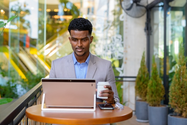 African businessman at cafe outdoors using laptop computer and holding coffee cup