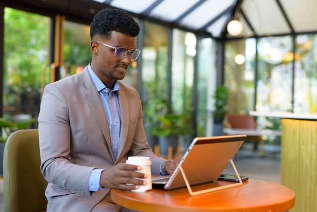 African businessman at cafe restaurant using laptop computer and holding coffee cup