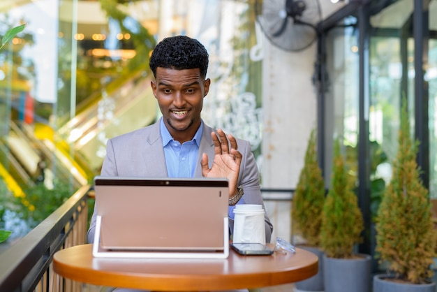 African businessman at coffee shop using laptop computer to make video call