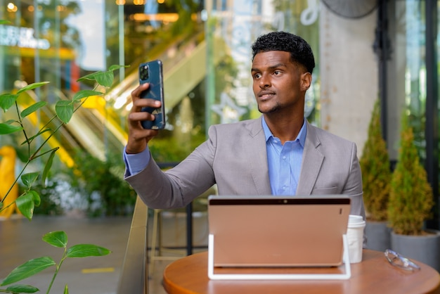 African businessman at coffee shop using laptop computer and taking selfie with mobile phone