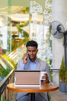 African businessman at coffee shop using laptop computer and talking on phone, vertical shot
