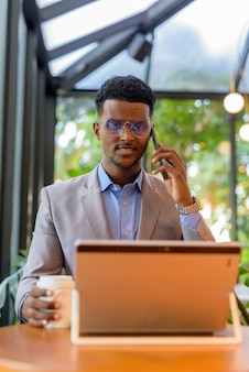 African businessman at coffee shop using laptop computer and talking on phone