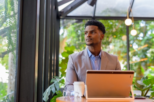 African businessman at coffee shop using laptop computer and thinking while looking through window