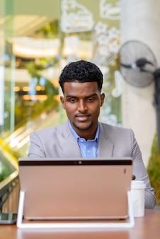 African businessman at coffee shop using laptop computer, vertical shot