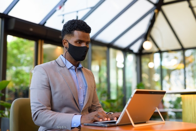 African businessman at coffee shop using laptop computer and wearing face mask