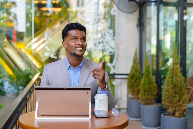 African businessman at coffee shop using laptop computer while smiling and pointing finger