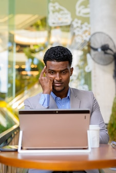 African businessman at coffee shop using laptop computer while thinking, vertical shot