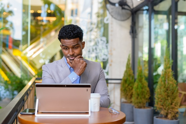 African businessman at coffee shop using laptop computer while thinking