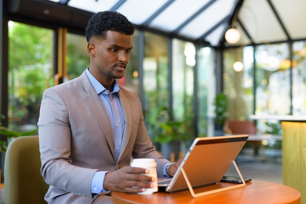 African businessman at coffee shop working using laptop computer