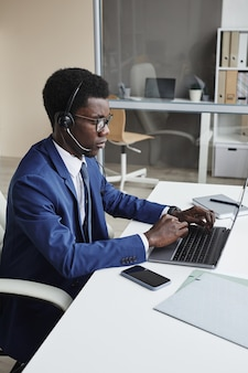 African businessman in headphones communicating online on laptop computer while working at the table in call centre