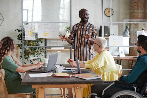 Африканский бизнесмен проводит бизнес-презентацию для своих партнеров, он рассказывает о стратегии финансового бизнеса