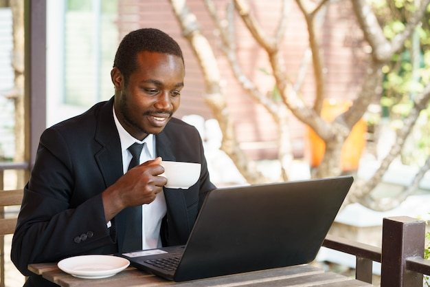 African businessman  holding coffee with smile and playing labtop.