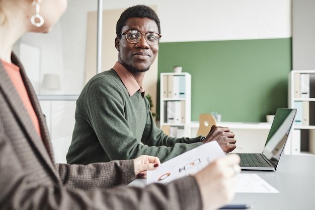 Африканский бизнесмен в очках разговаривает с бизнес-леди за столом, где они обсуждают финансовый отчет в команде
