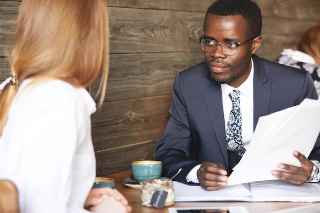Африканский бизнесмен берет интервью у кавказской женщины-кандидата на должность секретаря