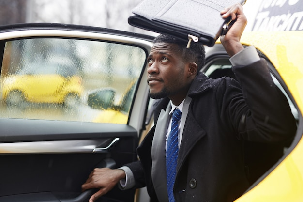 African businessman leaving taxi in rain