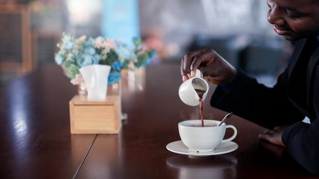 Африканский бизнесмен делает горячий кофе с улыбкой и счастливым