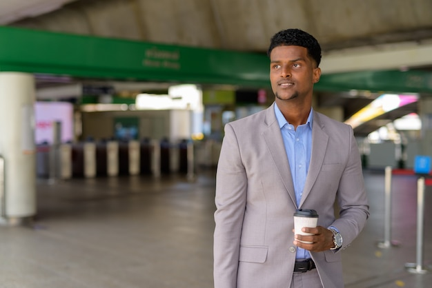 African businessman outdoors carrying cup of take away coffee while thinking