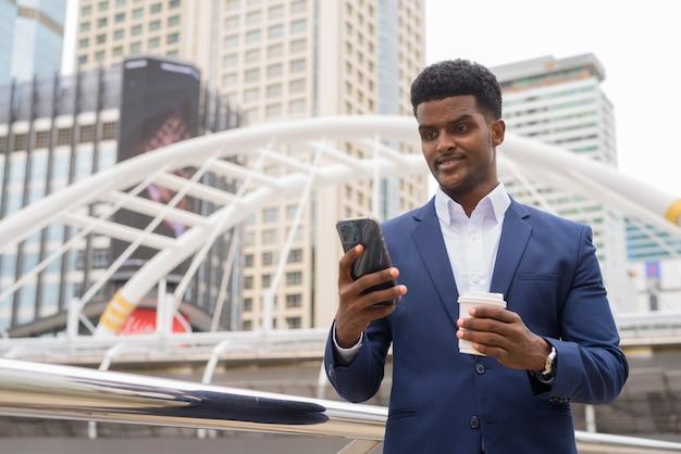 아프리카 사업가 야외에서 휴대 전화를 사용하고 들고 커피 컵, 가로 샷을 빼앗아