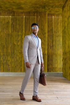 African businessman outdoors walking and looking stylish and cool full length shot
