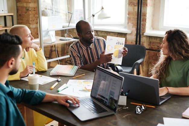 Африканский бизнесмен, указывая на финансовый документ и обсуждая его вместе со своими коллегами во время деловой встречи в офисе