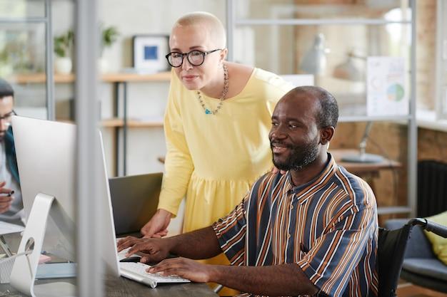 Африканский бизнесмен сидит на своем рабочем месте и консультируется со своим коллегой во время работы на компьютере с онлайн-презентацией