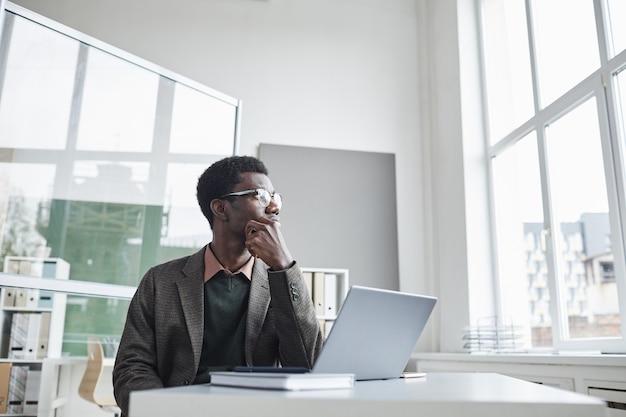 Африканский бизнесмен сидит за столом перед ноутбуком и думает о новых идеях в офисе