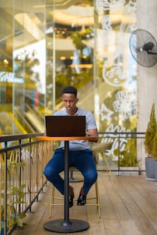 African businessman sitting at coffee shop while using laptop computer and social distancing