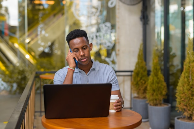 African businessman sitting at coffee shop while using laptop computer and talking on mobile phone