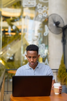 African businessman sitting at coffee shop while using laptop computer