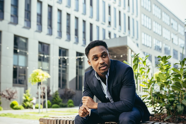 African businessman sitting frustrated on bench upset smoking marijuana cigarette to relieve stress and calm nerves during lunch break