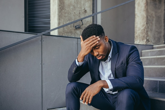 African businessman sitting frustrated on the stairs depressed by the results of his work, holding hands behind his head