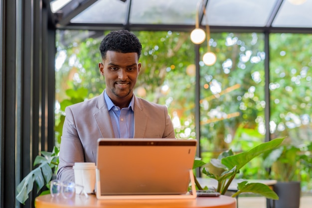 African businessman smiling at coffee shop while using laptop computer