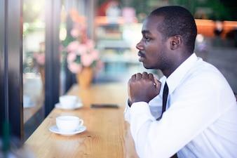 アフリカのビジネスマン精神的な平和的な祈りとコーヒーショップで願っています。ハイキースタイル