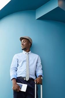 彼は飛行機で旅行する予定のスーツケースとチケットを持って立っているアフリカのビジネスマン