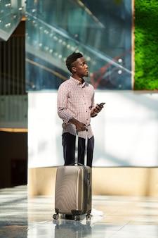 スーツケースを持って立って空港で彼の飛行を待っているアフリカのビジネスマン