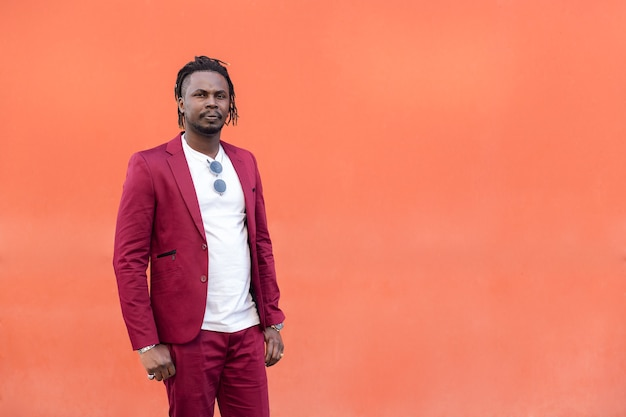 African businessman in suit with afro posing looking at camera in front of a red background, copy space for text