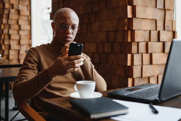 Африканский бизнесмен разговаривает по телефону, сидя за столиком в кафе, занятый предприниматель, удаленно работающий в кофейне с бумагами для ноутбука, разговаривает по мобильному телефону, темнокожий мужчина звонит во время обеда в кафетерии