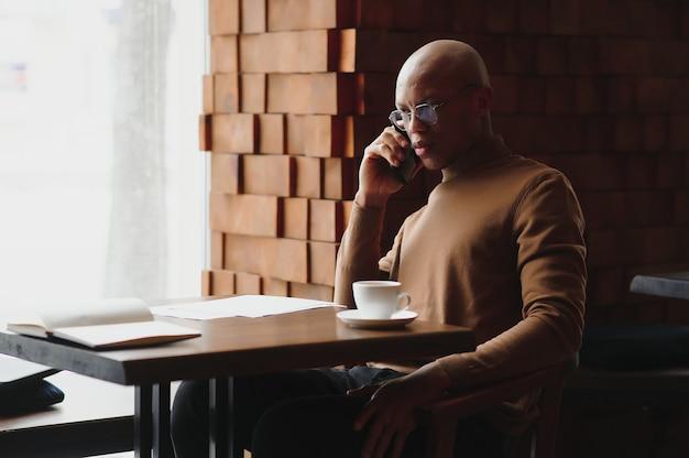 カフェのテーブルに座って電話で話しているアフリカのビジネスマン、モバイルで話しているラップトップの紙とコーヒーハウスで遠くで働いている忙しい起業家、カフェテリアで昼食をとっている黒人男性