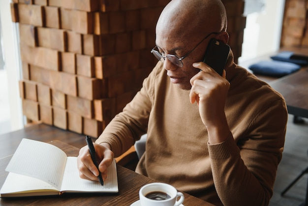 African businessman talking on phone sitting at cafe table, busy entrepreneur working distantly in coffee house with laptop papers speaking on mobile, black man making call having lunch in cafeteria